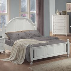 Wood panel bed with arched headboard and chamfered trim.Product: BedConstruction Material: Wood and veneers