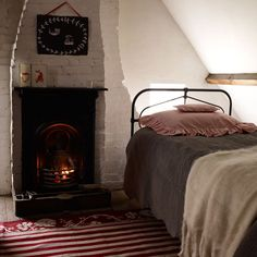 The woollen bed throws and accents of red  give this sweet and humble cottage bedroom  some cosy warmth.
