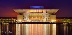 Das Opernhaus spiegelt sich in der Abenddämmerung im Wasser in Kopenhagen, Dänemark.