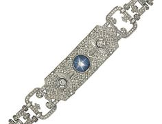 An Art Deco platinum, star sapphire and diamond bracelet   The central collet-set cabochon star sapphire to a pierced, articulated panel of geometric design millegrain-set with old single-cut diamonds, between diamond pierced panel articulated shoulders each set in the centre with an old brilliant-cut diamond collet, to a brilliant and baguette-cut diamond articulated tapering back, circa 1925, 17.0cm long