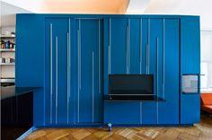 O metro quadrado em Nova York é altamente valorizado, neste projeto o escritório de arquitetura Normal Projects conseguiu aproveitar ao máximo o espaço de 42 m2. O apartamento localizado no Upper West Side, em Nova York, possui uma cozinha com amplo balcão, espaço para uma cama de casal, home office, biblioteca e closet. Tudo isso graças a parede azul vibrante de marcenaria feita sob medida que possibilita englobar tantas funções em um espaço tão pequeno.