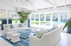 Contemporary living room with wall-to-wall patio doors and white truss ceiling. l Coastal Living Rooms l www.DreamBuildersOBX.com