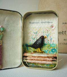 Artwork in a small Pastilles tin . Blackbird singing, with hand embroidery