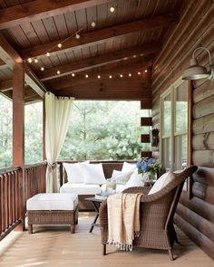 String lights from Target twinkle over the front porch of this Ohio lake house, and Pottery Barn wicker furniture surrounds an antique folding table, where the family plays cards.   - HouseBeautiful.com
