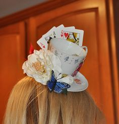 alice in wonderland teacup hat client pic 1 by spookykitten, via Flickr The hand of playing cards arranged behind the cup and saucer is so cute.