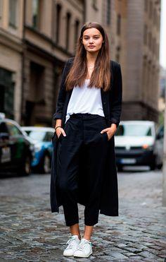 Street style de look comfy com blusa branca, calça cropped preta e maxi casaco preto