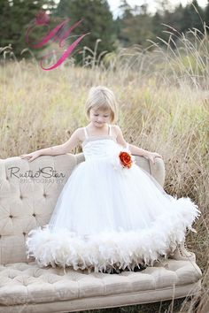 Couture, Beautful Flower Girl Dress, seven layers of Bridal Tulle, Gorgeous hand sewn beading on the bodice, Corset Laced up back.Array of Top Quality Feathers around the hem line.Detachable brooch, feathers and flower color of your choice.Sizes: 2 - 46 extra $12.008 extra $16.0010 -12 extra $28.00Dress can be made in white or ivory.Stunning for that special occasion!Chest Sizes1/2 years  22