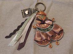 Porte clés en forme de poupée réalisée avec des capsules de café Nespresso orange et du fil d'aluminium.  Le porte-clés est décoré avec une breloque en bronze et des ruba - 16228383