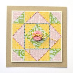 Make a quilt square pattern on a card using pattern paper and stitching.