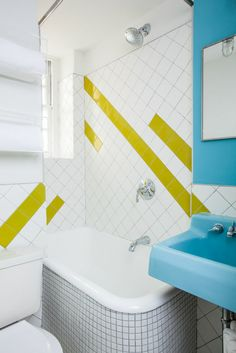 Renovated Upper East Side apartment. A gut renovation of a 400-square-foot apartment on the Upper East Side of Manhattan yielded a bright new bathroom. Complementing the tiny, apartment-sized bathtub is a salvaged porcelain sink and new white tile, plus graphic tile inserts that draw the eye to colorful moments in the space. Photo by Alan Gastelum.