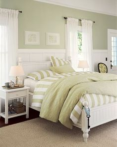 sage green accent wall behind the all white bed, with green