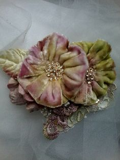 Lovely tattered shabby Brooch/corsage/hair accessory, featuring hand created and hand dyed silk velvet blooms in muted purples and greens with gold and diamante centres. Surrounding the main blooms, I have used a , a velvet leaf, and some hand dyed hand sewn pearl applique lace,
