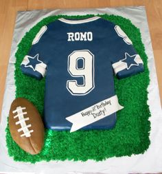 Football Jersey Cake - This is a Dallas Cowboys (Tony Romo) jersey cake for a birthday. It is a chocolate fudge cake covered in fondant with fondant and royal icing decorations, grass is buttercream and the football is made of crispy treats.