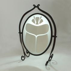 #KHEPRI.   Extra-clear mirror with sand-blasted inserts that create a beetle-shaped design. The structure is in wrought iron forged by a master blacksmith.