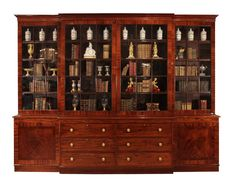 A magnificent and large scale English 18th century Regency period mahogany breakfront cabinet. This very impressive cabinet is raised on a solid plinth base that protrudes at the center, housing six drawers with brass knobs and keyhole escutcheons. On either sides are two flamed mahogany paneled doors that open to reveal an adjustable shelf. Each of the extraordinary four doors above, have fifteen individual hand blown original glass panes, within mahogany frames. All below a handsome molded…