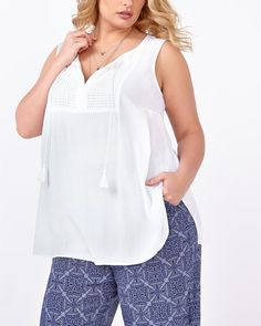 """Spring forward in this light plus-size top from d/c JEANS! Crafted from a soft, fluid fabric, it has a split neck with tassels, crochet detailing, wide straps, side slits and a flattering fit. Wear it with a printed pant! Length: 31"""" at front, 30"""" at back"""