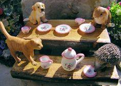 Miniature animal figurines enjoy a tea party picnic in our miniature fairy garden.