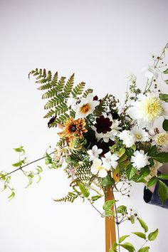 Late summer bouquet with green, mustard and white flowers, clematis vine and fern foliage