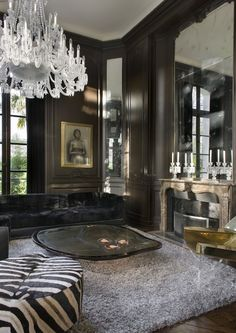 a glamorous chandelier balances the masculine aesthetic of this room