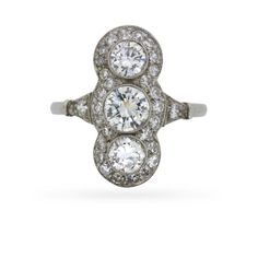 In a style evocativeof decades past, this dazzling circa 1950s three stone diamond ring scintillates with 1.80 carats of stunning F colour, VS clarity diamonds. Centrally-set with a vertical trio of round brilliant cut diamonds totalling 1.20 carats,a singlerow of grain-set eight cut diamonds traces the ring's outer edge with one further diamond punctuating each …