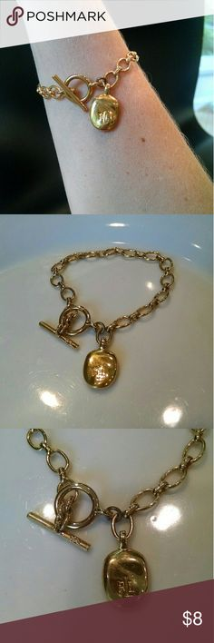 Ralph Lauren bracelet Cute gold chain and toggle bracelet. Charm has Ralph Lauren logo on it. It is not too lightweight, which makes me think it is gold plated, except for one small link near the charm that does not seem to match the rest of the bracelet well. Otherwise, good quality. 7.25 inches long. Received as a gift and wore it once, but I am really a silver girl ;) Ralph Lauren Jewelry Bracelets