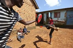 A trainer helps Kirabo Beatrice as she rehearses her acting moves during a martial arts class organised by local non-governmental organisations (NGOs) and residents, in the Wakaliga slums of Uganda's capital Kampala, November 1, 2014. (REUTERS/Edward Echwalu)