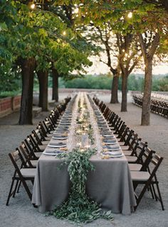 Beautiful rustic outdoor wedding reception set up with a long table and floral runner.