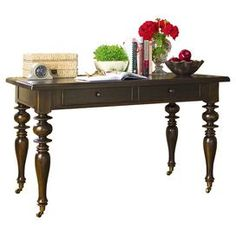 """A perfect addition to your den or home office, this lovely wood writing desk showcases a drop-front compartment and turned caster legs.   Product: DeskConstruction Material: WoodColor: Tobacco   Features: Part of the Paula Deen Home CollectionDistressed finish Turned legsBottom castersDrop-front drawer     Dimensions: 30"""" H x 50"""" W x 26"""" DNote:  Accents pictured are not included"""