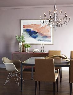 """""""We painted the dining room ceiling the same dark and sophisticated color as the walls for an all-encompassing experience,"""" says Frampton of Benjamin Moore's Wet Concrete hue. """"Then we lightened the room with pops of color from the bright artworks."""" Here, a painting by Lauren Adams is mounted above a Lawson Fenning chest; the chandelier is by Gino Sarfatti for Flos."""