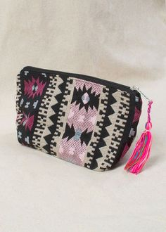 This black and white aztec with hints of pink, blue, and maroon zip up pouch…