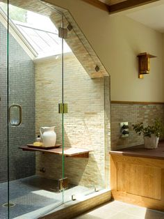 skylight in the shower!  Bathed in Light - new to bathroom design is the combination of unlike tiles. In this case a slate blue glass tile lines the back wall and floor, and a textured stone tile is used on the sidewalls and elsewhere in the bathroom. The glass almost gives a waterfall effect next to the stone.