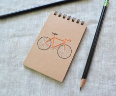 Bike notebook with hand embroidered cover. Listing is for ONE mini-notebook. Choose from six different color bike frames, red, orange, yellow, green, blue, or purple. If theres another color youd like, send me a message and Ill do my best to accommodate you. Notebook is spiral-bound