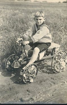 PLAY: 1900's Boy with Peddle Car .  That boy pull handle to may it go .He sterling with his feet . I know I had one . LINTON.