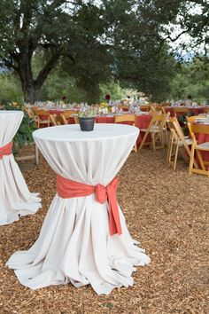 Round cocktail tables with white table cloths and a burnt orange bow.