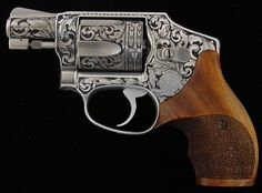 """Smith & Wesson Engraved .38 special stainless steel finish 2"""" barrel with full coverage engraving and custom wood stocks."""