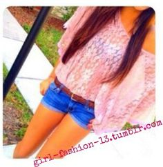 Pink sheer loose blouse tucked into belted shorts.