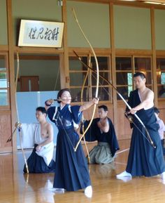 A woman dressed in a hakama stands with bow drawn, while other archers are kneeling down in the background