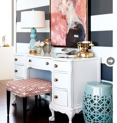 Within the first week of moving into her new place, Lindsay had painted eight-inch-wide stripes to create a feature wall in the living room. In the end, the thick charcoal grey stripes make a statement, while corals in the painting and stool fabric punch up the look. I like this girl's style.