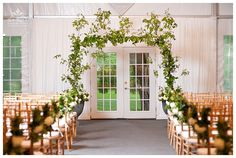 Ah, Mother Nature is a fickle creature, after nearly completing the setup outside... we had to do a flip to the wonderful indoor space at Shully's. A beautiful shot that captures the entire ceremony backdrop. Florals by Stephanie McCready. Photography compliments of Linda at Boutique Photographer - www.boutiquephotographer.com.