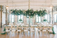 Garden inspired wedding reception at The Cedar Room in Charleston, SC! Gold chiavarri chair, gold rimmed chargers, a floral garland runner and a hanging floral chandelier above the head table! *** Aaron and Jillian Photography