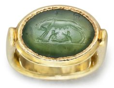 Roman Chrome Chalcedony Ringstone with Lupa Romana, C. 1st Century BCThe convex oval stone engraved with the she-wolf suckling the twins Romulus and Remus, on a groundline, two Greek letters in the field above, T ?, likely the initials of the original owner; mounted as a ring in a modern gold setting.