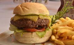 Hambúrguer de Fraldinha com queijo gruyère, chips de presunto cru, cebolas roxas grelhadas, alface americana e tomate no pão acompanhado de fritas, maionese maison e BBQ, servido mal passado