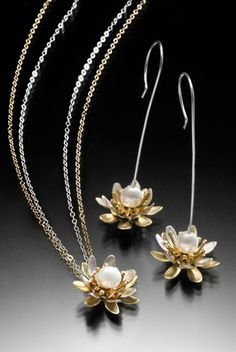 Lotus Flower Necklace & Earrings Elegant silver and brass lotus petals spin independently around the fresh water pearl centers. Contemporary and classic at the same time!