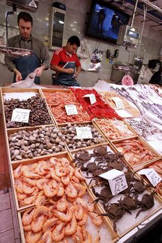 Two fishmongers wait for customers at their fish and seafood shop at a market in Madrid. Traditional markets are still a part of the Spanish way of life, and many are distributed through the city. A visit to one of these markets will reveal a large selection of quality vegetables, meat and much of the traditional way of life.