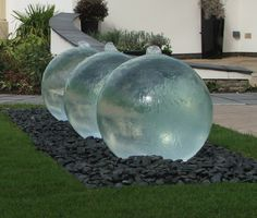 "This ""Triple Bespoke Glass Sphere Water Feature"" by Tills Innovations in the UK uses a poly-carbonate sphere that fills with water and has water flowing down the outside of the sphere."
