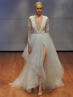 Rivini tiered A-line wedding dress with translucent cascading skirt, high slit, plunging v-neckline and sheer long sleeves from Fall 2016 | https://www.theknot.com/content/rivini-wedding-dresses-bridal-fashion-week-fall-2016