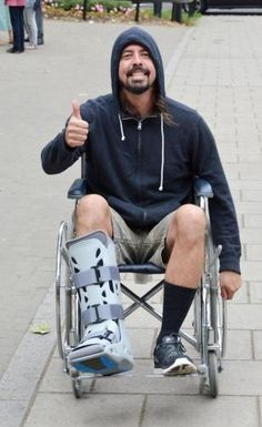 Dave Grohl gave a thumbs up and a smile as he was spotted in a wheelchair Sunday in London.