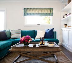 Teal velvet sofa, natural fiber rug, white backdrop.
