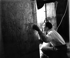 Howard Carter looking through the doors of the second shrine which was constructed from 16 parts gilded w/gold inside and out.Jan, 4, 1924