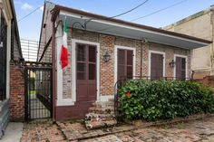 The three-bedroom home has exposed brick interiors and a large, grassy backyard. Cottages With Pools, Greek Revival Home, Creole Cottage, Brick Cottage, Brick Interior, Gas Lanterns, Gas Lights, Dormer Windows, Copper Lighting